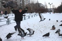 Little baby boy rides in the Park of birds pigeons in winter laughs fun emotions stock photo
