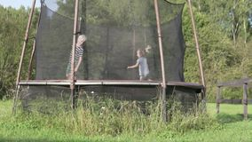 A boy with a little girl jumping on a trampoline in the summer at the cottage stock video footage