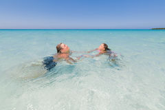 Boy and little girl relaxing, swimming and enjoying there leisure time in the ocean Stock Photography