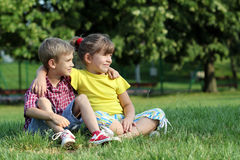 Boy and little girl sitting on grass Royalty Free Stock Images