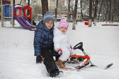 The boy with a little girl sitting on a sled. Stock Photos