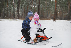 The boy with a little girl sitting on a sled. Stock Photography