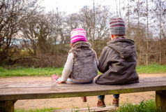 Boy and little girl talking sitting on a bench Royalty Free Stock Photos