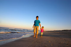 Boy and little girl walk along coastline Royalty Free Stock Photo