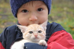 Boy with little kitten outdoor in fall Stock Photo