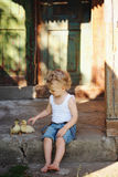 Boy with little yellow duckling in summer village Royalty Free Stock Photos