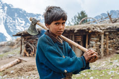 Boy living in the Himalayas holding an axe
