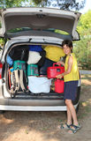 Boy loads the luggage in the trunk of the car. Young boy loads the luggage in the trunk of the car during the trip of the summer holidays Royalty Free Stock Images