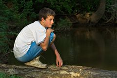 Boy on Log. Teenage boy crossing river on a log Royalty Free Stock Images