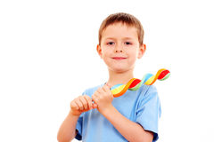 Boy with lollipop. 6-7 years old boy with lollipop on white - kids royalty free stock photo