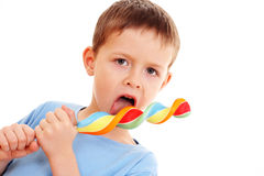 Boy with lollipop. 6-7 years old boy with lollipop on white - kids royalty free stock images