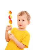 Boy with lollipop. 4-5 years old boy with lollipop on white - kids stock image