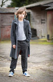 Boy in Long Coat Standing in a Farm Yard Stock Photo