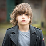 Boy in Long Coat Standing in a Farm Yard Royalty Free Stock Images