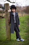 Boy in Long Coat and Top Hat. Portrait of a boy with long hair in a long coat and top hat standing isolated in a farm yard leaning against a pole Stock Photo