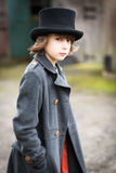 Boy in Long Coat and Top Hat. Portrait of a victorian styled boy in a long coat and wearing a top hat against a blurry back ground. Steampunk themed Royalty Free Stock Image