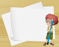 A boy with a long pencil standing beside the empty papers Stock Photo