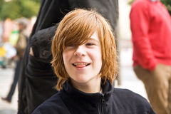 Boy with long red hair pokes his tongue as a joke. And smiles Stock Images