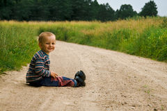 Boy and a long walk. Small boy sitting on the road having a rest after a long walk Stock Image