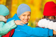 Boy look back with his friends hugging close Stock Photos