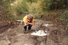 Boy look into the puddle on the country road Stock Images
