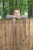 Boy looking from above a fence. Royalty Free Stock Photo