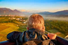 Boy looking from air balloon during flight. Laos. Stock Photos