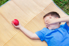 Boy looking at apple and covering eye by hand. Boy laying on mat, looking at red apple and covering his eye by hand royalty free stock photo