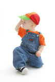Boy looking away. Boy with hat and overalls stock photo
