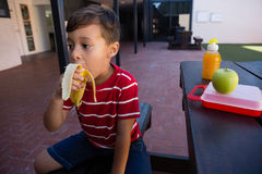 Boy looking away while eating banana at table. In school Stock Photo