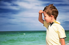 Boy looking away from his palm on the background of cloudy sky a. Nd sea horizontal Royalty Free Stock Photos