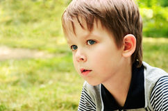 Boy looking away with interest in the park. Horizontal Stock Image