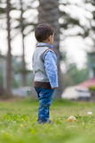 Boy Looking Away. A Little Boy Looking Away Standing on Green Grass Royalty Free Stock Image