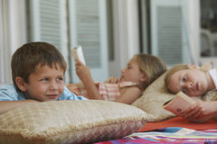 Boy Looking Away With Sisters Reading Books At Porch. Little boy looking away while lying at porch with sisters reading books in background Stock Image