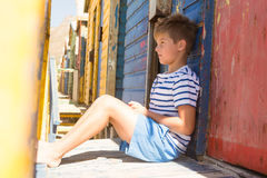 Boy looking away while sitting by beach hut. Side view of boy looking away while sitting by beach hut Stock Photography