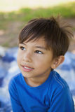Boy looking away in thought at park. Close-up of a cute young boy looking away in thought at the park Stock Photos