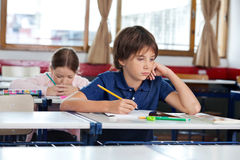 Boy Looking Away While Writing In Book. Little boy looking away while writing in book with classmate studying at classroom Stock Photography