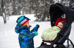 Boy Looking at Baby in a Stroller in a Snowy Forest Stock Photography