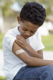 Boy Looking At Bandage On Arm Stock Photography