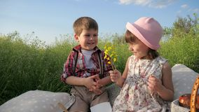 Boy is looking at beautiful girl, closeup portrait, boy is giving flowers to pretty girl, young couple in love, two. Adorable children in sunny park, happy stock footage