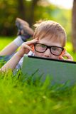 Boy looking from behind laptop in the partk Stock Photo