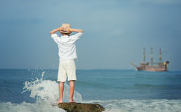 Boy looking on big old ship on the sea Royalty Free Stock Photography