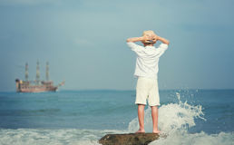 Boy looking on big old ship on the sea Stock Images