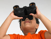 Boy looking through the binocular stock photography