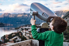 Boy looking through binocular at the city of Kotor, Montenegro Stock Photos