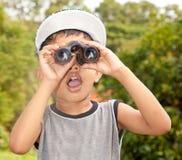Boy looking through binoculars. A boy looking through binoculars and spotting something Stock Image