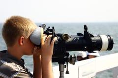 Boy looking through binoculars. A young boy looking through a pair of Navy binoculars Stock Image