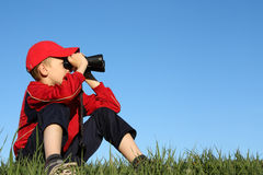 Boy looking through binoculars. On top of hill royalty free stock photography