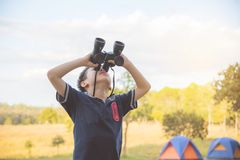 Boy looking by binoculars at camping site Stock Photos