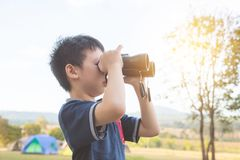 Boy looking by binoculars at camping site Stock Photo